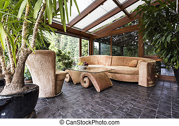 Stylish orangery with potted plants, glazed roof and unique...