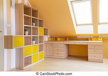 Sunny attic home office with wooden bookcase, desk and big...