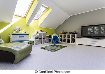 Child room at the attic with TV set, bed, chest of drawers...