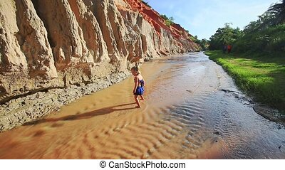 Small Blond Girl Walks Backward in Stream Shallow Water -...