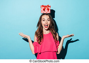 Girl in dress with a gift box on her head