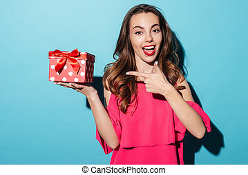 Smiling girl in dress pointing finger at a gift box