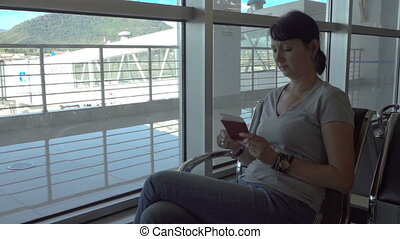 Woman checks her ticket in the airport waiting area.