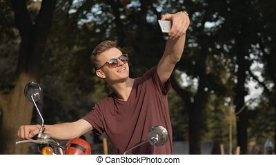 Biker Mekes Selfie - Young attractive man wears sunglasses...