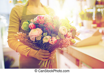 close up of woman holding bunch at flower shop - people,...