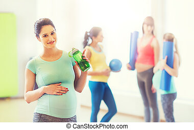 happy pregnant woman with water bottle in gym