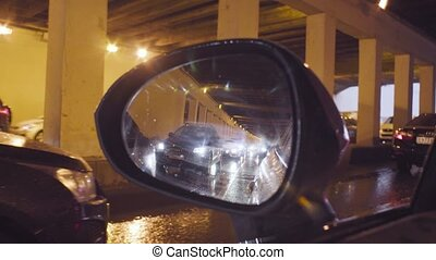 View in car's rearview mirror in tunnel