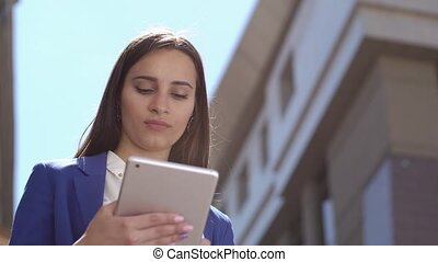 Business woman reads something on the tablet standing in the city