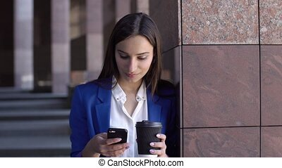 Business woman checks her phone standing in the city