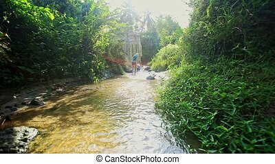 Mother and Daughter Walk along Stream between Green Banks -...