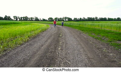 Two kids running together on rural road, slow motion