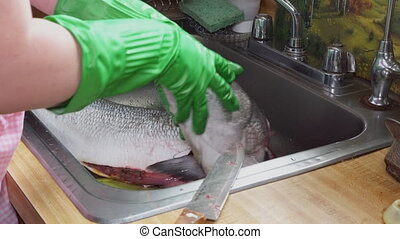 Cook cleaning blyufish on the scales a wooden cutting board