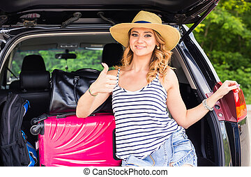 Travel, tourism - woman sitting in the trunk of a car with suitcases, showing thumb up sign, ready to leave for vacations.