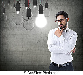 Thoughtful businessman looking at light bulb - Thoughtful...