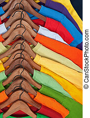 Choice of colorful casual clothes on wooden hangers