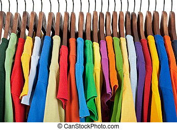 Variety of multicolored clothes on wooden hangers