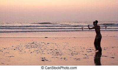 Unidentified man spinning pole on the beach. - Goa, India -...