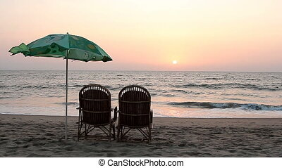 Two chairs and umbrella near coastline at sunset time - Goa,...