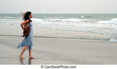 Unidentified woman dancing on the beach.