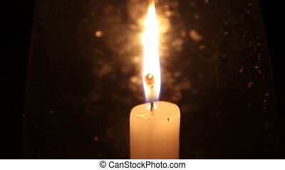 Bright burning candle in the dark