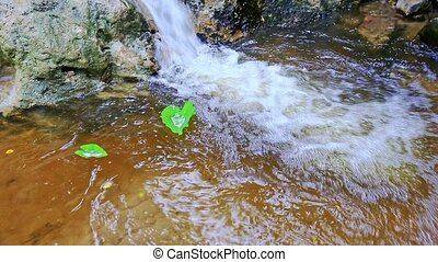 Green Leaves Twist on Water Surface by Waterfall - Camera...