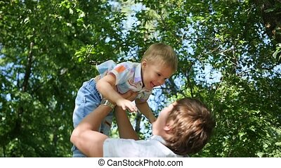 Slow motion. a young father throwing his laughing baby up in the air. Outdoor recreation