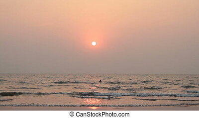 couple is swimming in the ocean at sunset
