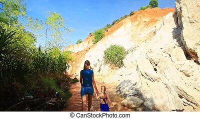 Mother Girl Remove from Camera Walking along Stream -...