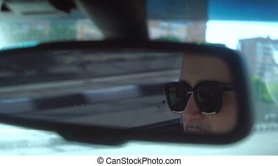 man in the car rides view from rear-view mirrors - young man...