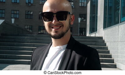 Young fashionable business man in sunglasses smiling on camera
