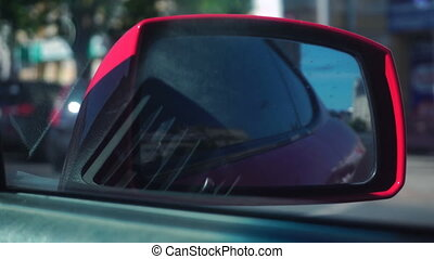 road view in the backview mirror of a red car close up