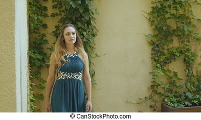 Young woman in grey evening dress and high heels walks in...