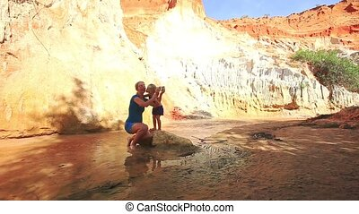 Little Girl Kisses Mother Squatting at Rock Making Selfie -...