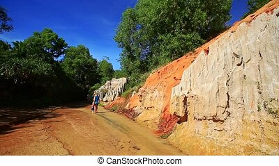 Mother and Daughter Walk along Steep Orange Cliffs - Distant...