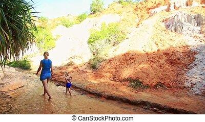 Little Blond Girl Runs along Water Stream Beside Mother