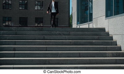 business man goes down the stairs in the street at bright...