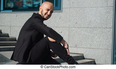 Happy young man smiling on camera and waering a black...