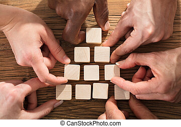 People Arranging Block On Pyramid - Close-up Of A People...