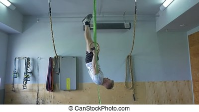Muscle ups rings man swinging workout exercise at gym. Sport, fitness, training and people concept, man exercising and doing ring pull-ups in gym