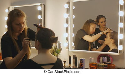 Makeup artist backstage. Reflection in lighted makeup mirror...