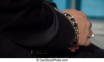 guy rolls up sleeves on a black jacket - close up of a guy...