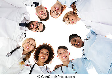 Happy Medical Team Forming Huddle - Low Angle View Of Happy...
