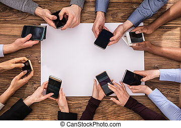 Elevated View Of Businesspeople Hand Using Mobile Phone With...