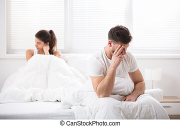 Worried Couple Sitting On Bed