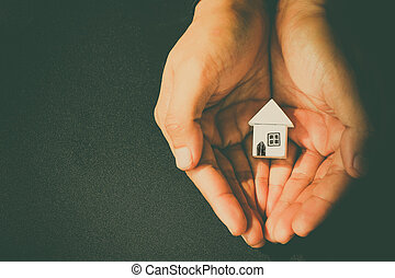 hand hold home model - Woman hands holding house model, eco...