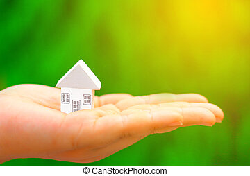 hand hold home model - Woman hands holding home model with...
