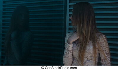 girl looks at his reflection in the glass on the street -...