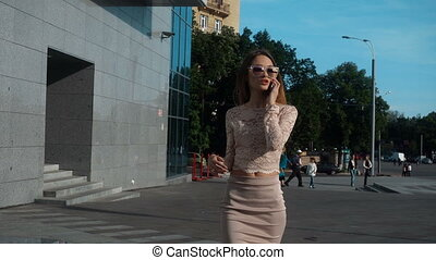 Cute young business girl in fashionable dress and sunglasses...