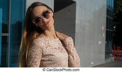 girl with bright glasses smiling revolves around herself and...