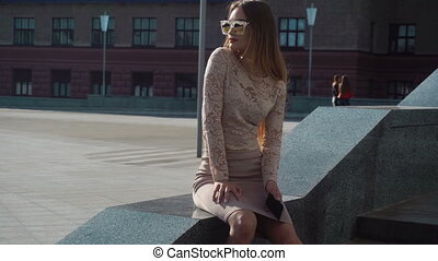 young blonde girl in golden sunglasses sits in the street -...
